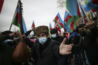An Azerbaijani man dances as other hold national flags as they celebrate the transfer of the Lachin region to Azerbaijan's control, as part of a peace deal that required Armenian forces to cede the Azerbaijani territories they held outside Nagorno-Karabakh, in Aghjabadi, Azerbaijan, Tuesday, Dec. 1, 2020. Azerbaijan has completed the return of territory ceded by Armenia under a Russia-brokered peace deal that ended six weeks of fierce fighting over Nagorno-Karabakh. Azerbaijani President Ilham Aliyev hailed the restoration of control over the Lachin region and other territories as a historic achievement. (AP Photo/Emrah Gurel)