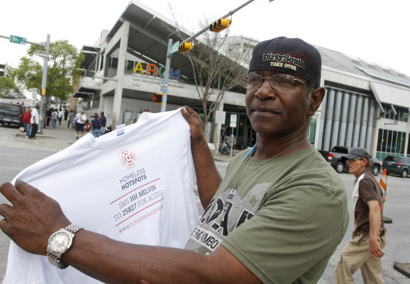 "Melvin Hughes, a homeless man hired by BBH Labs to provide and promote a mobile 4G Wi-Fi service during SXSW, holds the T-shirt he was given by the marketing agency in Austin, Texas on Tuesday, March 13, 2012. A charitable marketing program that paid homeless people to carry Wi-Fi signals at South By Southwest has drawn widespread debate at the annual Austin conference and around the country. BBH Labs, a unit of the global marketing agency BBH, gave 13 people from Austin's Front Steps Shelter mobile Wi-Fi devices and T-shirts that announced ""I am a 4G Hotspot."" (AP Photo/Jack Plunkett)"