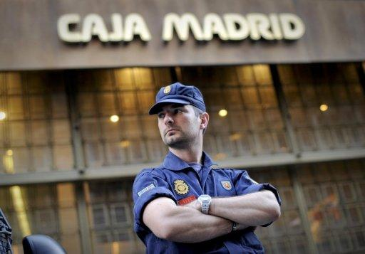 A policeman stands guard on May 14 outside Caja Madrid's headquarters in Madrid