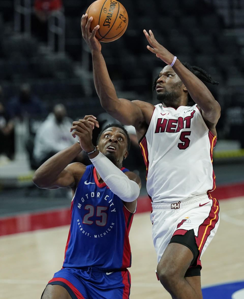 Miami Heat forward Precious Achiuwa (5) makes a layup as Detroit Pistons forward Tyler Cook (25) defends during the first half of an NBA basketball game, Sunday, May 16, 2021, in Detroit. (AP Photo/Carlos Osorio)