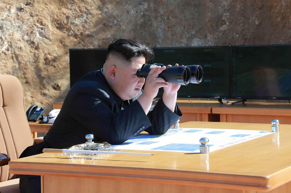 North Korean leader Kim Jong-Un holds binoculars.