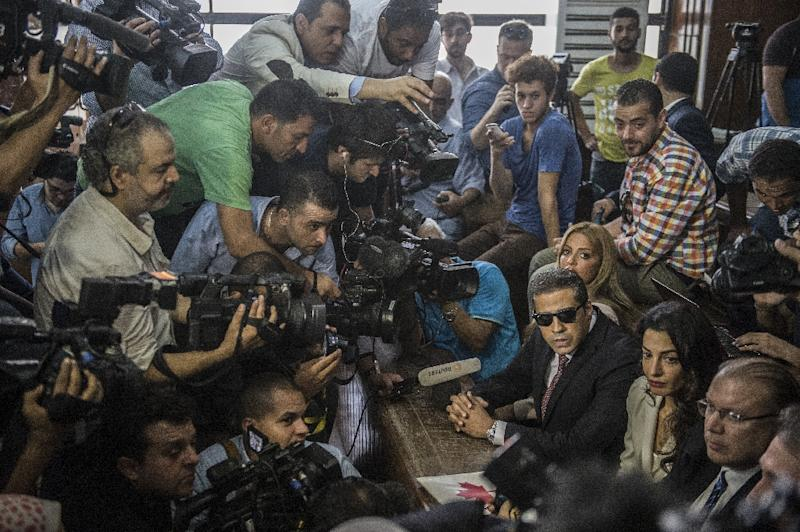 Al-Jazeera journalists Mohamed Fahmy (bottom, 3rd from R) and Baher Mohamed (center, 2nd from R), talk to the press during their trial in Cairo on August 29, 2015 (AFP Photo/Khaled Desouki)