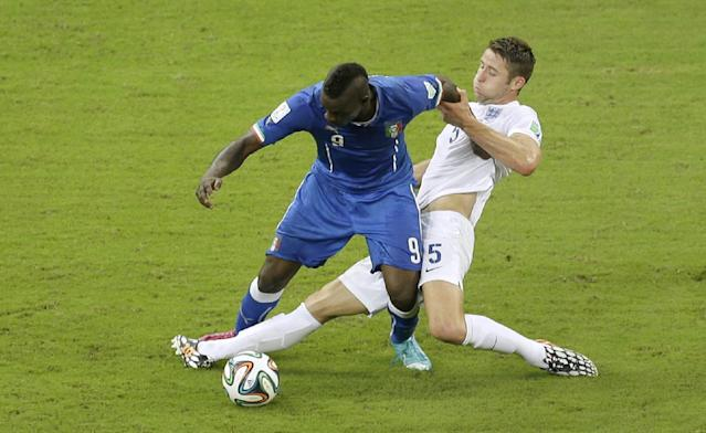 Italy's Mario Balotelli, left, challenges for the ball with England's Gary Cahill during the group D World Cup soccer match between England and Italy at the Arena da Amazonia in Manaus, Brazil, Saturday, June 14, 2014. (AP Photo/Themba Hadebe)