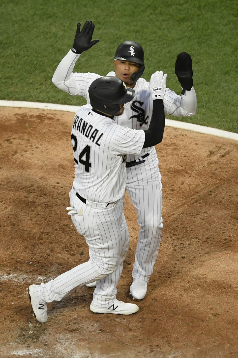 Chicago White Sox's Yasmani Grandal (24) celebrates with Yermín Mercedes at home plate after hitting a three-run home run during the second inning of the team's baseball game against the Minnesota Twins on Tuesday, May 11, 2021, in Chicago. (AP Photo/Paul Beaty)