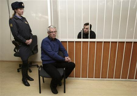 Greenpeace International activist Dziemianczuk of Poland, one of 30 people arrested over a Greenpeace protest at Prirazlomnaya oil rig, sits in a defendants' cage during a court session in St. Petersburg