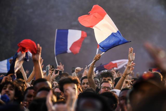 <p>People cheer and wave French flags as they gather at a fan zone in Paris on July 10, 2018 to watch the Russia 2018 World Cup semi-final football match between France and Belgium. (Photo by Eric FEFERBERG / AFP) </p>
