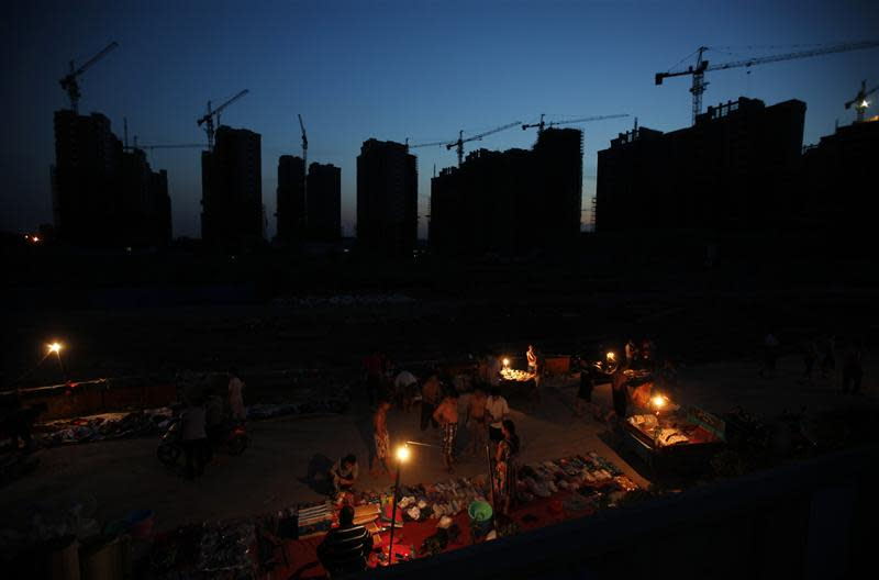 File photo shows migrant construction workers looking at goods sold by peddlers on a small street outside their dormitories near a residential construction site in Shanghai