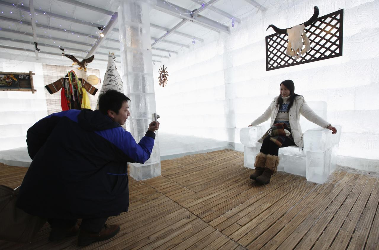 A couple takes a picture with a chair made of ice at the Ice Palace in Shangri-La Hotel in Harbin