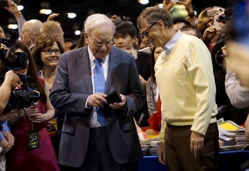 Berkshire Hathaway CEO Warren Buffett (L) gets his wallet out to pay a bet to Microsoft co-founder Bill Gates after participating in a newspaper throwing contest prior to the Berkshire annual meeting in Omaha, Nebraska May 2, 2015. REUTERS/Rick Wilking