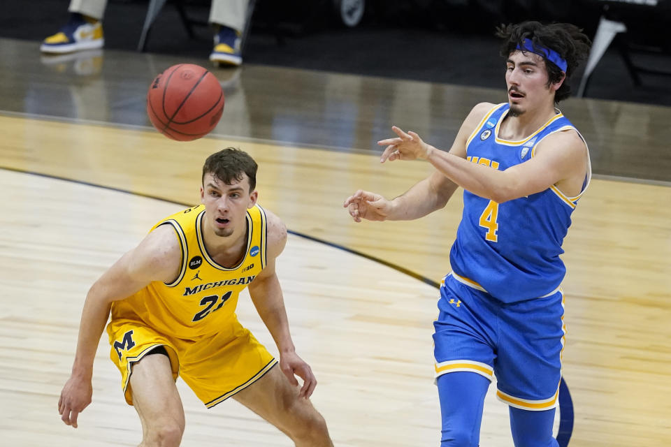 UCLA guard Jaime Jaquez Jr. (4) passes over Michigan guard Franz Wagner (21) during the first half of an Elite 8 game in the NCAA men's college basketball tournament at Lucas Oil Stadium, Tuesday, March 30, 2021, in Indianapolis. (AP Photo/Darron Cummings)