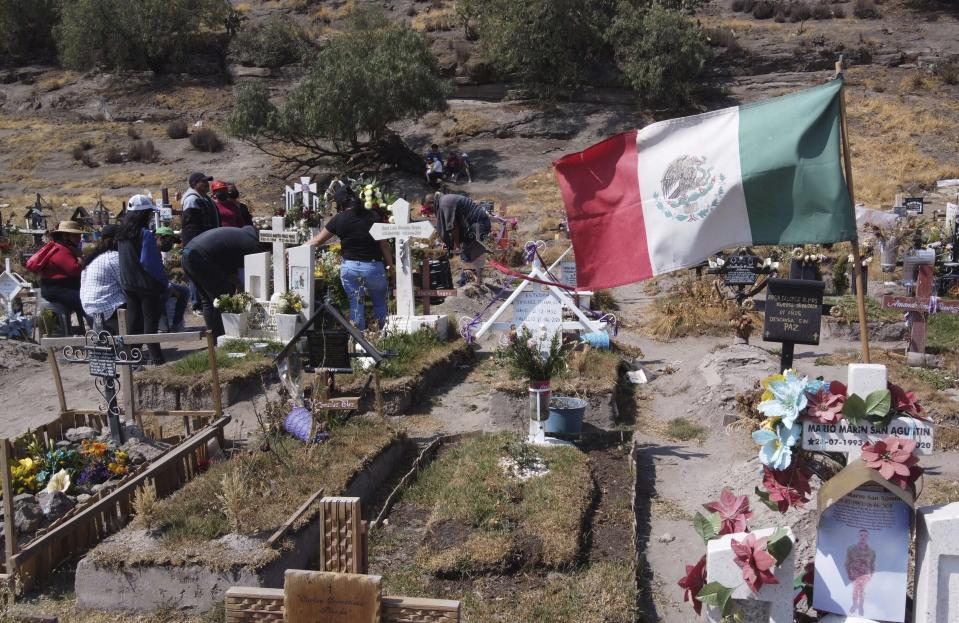 Family members attend the burial service of a relative who died of complication related to COVID-19, at the Valle de Chalco municipal cemetery on the outskirts of Mexico City, Saturday, Jan. 30, 2021. Due to the high number of recent deaths, many due to the new coronavirus pandemic, Mexico City's cemeteries are filled to capacity. (AP Photo/Christian Palma)
