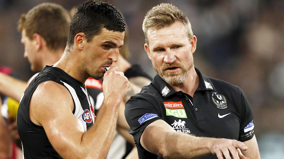 Seen here, Scott Pendlebury chats with Collingwood coach Nathan Buckley.