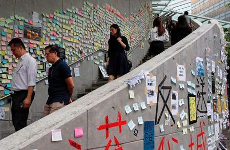 People walk past notes and placards with messages of support for the protest against the extradition bill in Hong Kong