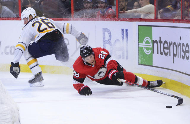 Ottawa Senators right wing Connor Brown (28) reaches for the puck as Buffalo Sabres defenceman Rasmus Dahlin (26) stops during the second period of an NHL hockey game Monday, Dec. 23, 2019, in Ottawa, Ontario. (Sean Kilpatrick/The Canadian Press via AP)