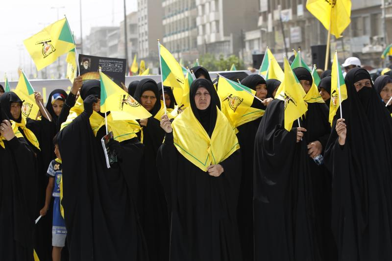 Iraqi Shiite Muslim women wave Iraqi Hezbollah flags during a parade marking the annual al-Quds Day in Baghdad