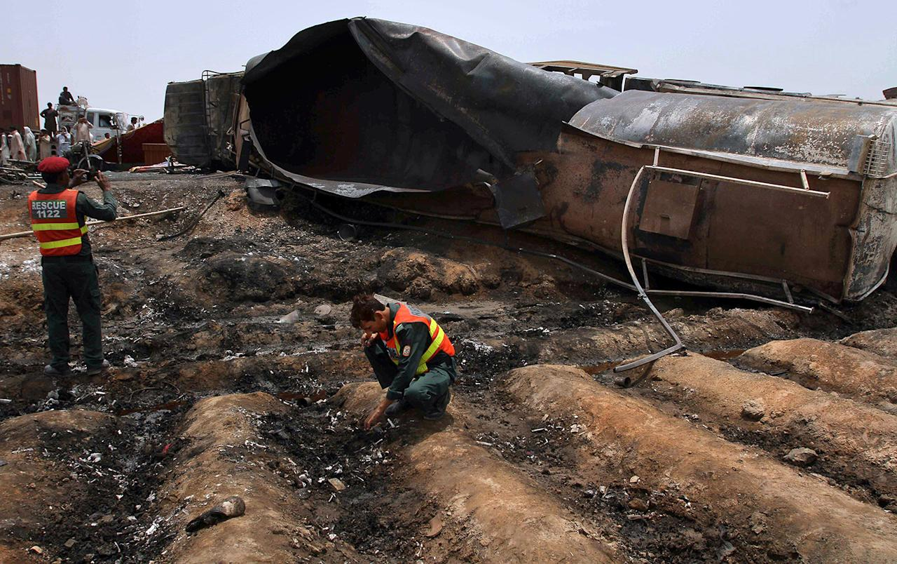 <p>Pakistani rescue workers examine the site of an oil tanker explosion at a highway near Bahawalpur, Pakistan, Sunday, June 25, 2017. An overturned oil tanker burst into flames in Pakistan on Sunday, killing more than one hundred people who had rushed to the scene of the highway accident to gather leaking fuel, an official said. (AP Photo/Iram Asim) </p>