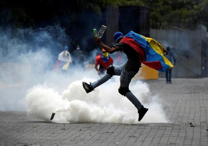 A supporter of Venezuelan opposition leader Juan Guaido is surrounded by tear gas shot by security forces in Caracas on March 10, 2020 -- despite US backing for more than a year, Guaido has failed to dislodge Maduro (AFP Photo/Federico Parra)