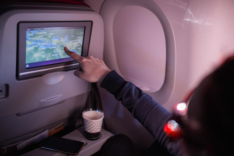 Young Woman Pointing on Map on Airplane Device Screen