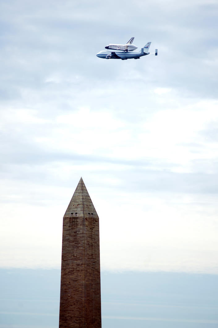 The Space Shuttle Discovery, attached to the back of a Boeing 747 airplane, passes over the Washington Monument, in Washington, Tuesday April 17, 2012. Discovery is en route from Kennedy Space Center to the Smithsonian National Air and Space Museum Udvar/Hazy Center at Dulles International Airport. (AP Photo/Cliff Owen)