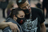 Michael Bailey, right, of Highland, Calif. embraces Joanna Fuentes, of Whittier, Calif., during a ceremony Thursday, Oct. 1, 2020, on the anniversary of the mass shooting three years earlier in Las Vegas. The ceremony was held for survivors and victim's families of the deadliest mass shooting in modern U.S. history. (AP Photo/John Locher)