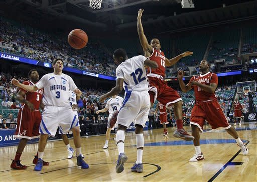 Alabama's Trevor Releford, right center, loses the ball as he is guarded by Creighton's Jahenns Manigat, center left, during the first half of a Midwest Regional NCAA tournament second-round college basketball game in Greensboro, N.C., Friday, March 16, 2012. (AP Photo/Gerry Broome)