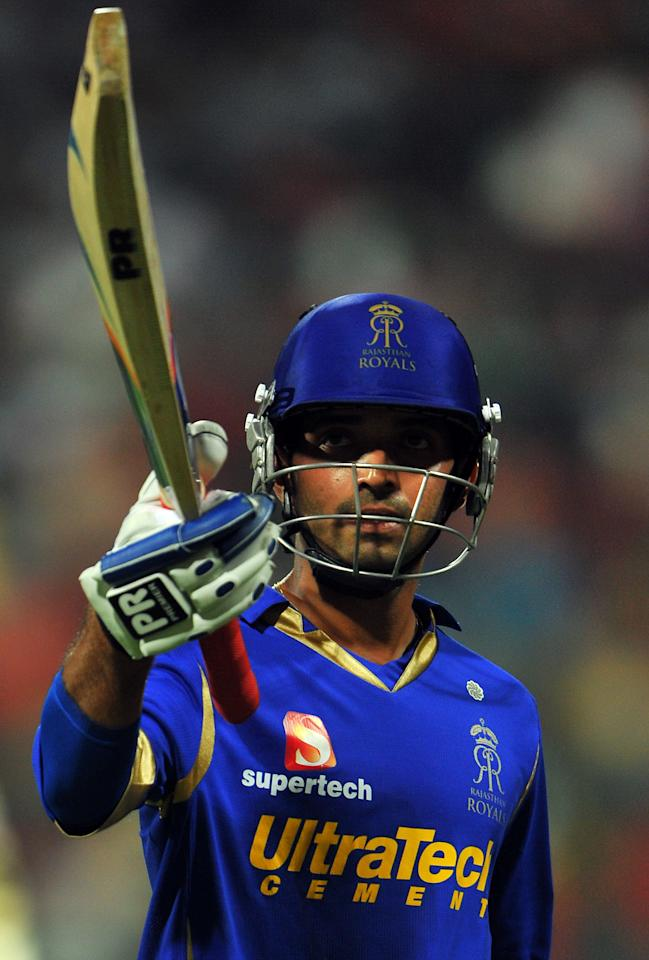 Rajasthan Royals batsman Ajinkya Rahane raises his bat to acknowledge the cheering crowd after scoring the IPL 5's first century during the IPL Twenty20 cricket match between Royal Challengers Bangalore and Rajasthan Royals at the M. Chinnaswamy Stadium in Bangalore on April 15, 2012.     RESTRICTED TO EDITORIAL USE. MOBILE USE WITHIN NEWS PACKAGE.    AFP PHOTO/Manjunath KIRAN (Photo credit should read Manjunath Kiran/AFP/Getty Images)