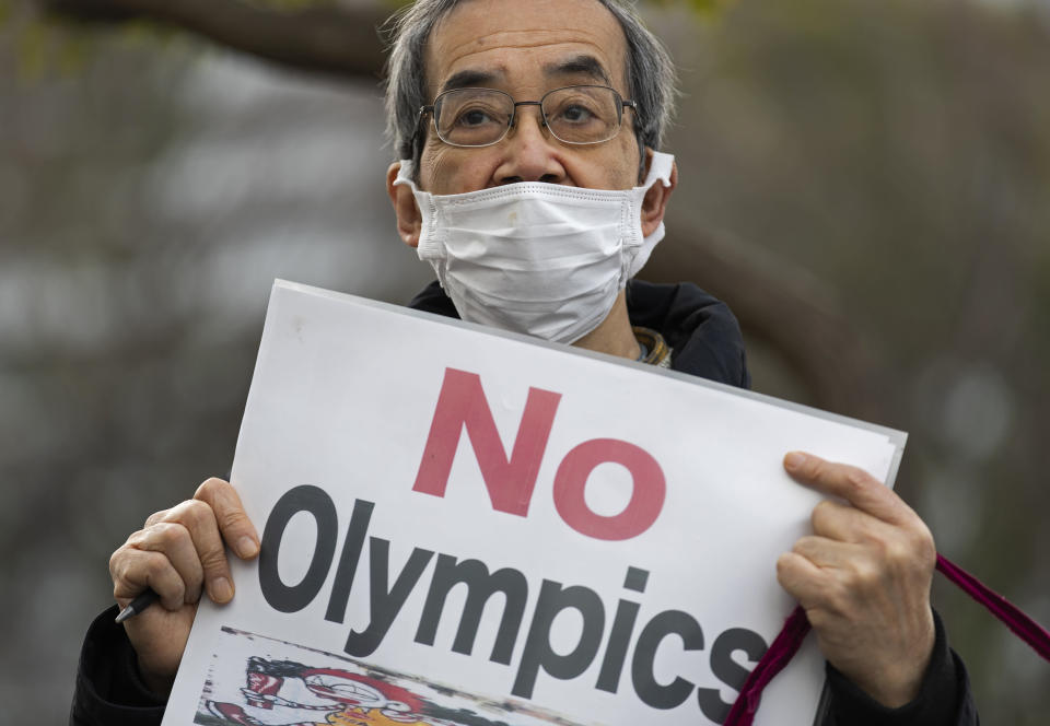 A demonstrator holds a placard protesting the planned Tokyo 2020 Olympic games near a building where Yoshiro Mori was meeting to announce his resignation as the president of the Tokyo Olympic organizing committee in Tokyo on Friday, Feb. 12, 2021. Mori resigned Friday, following sexist comments implying women talk too much. (AP Photo/Hiro Komae)