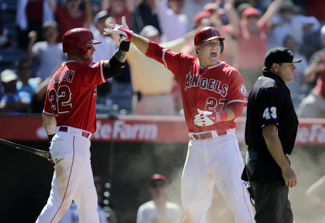 Los Angeles Angels' Mike Trout, right, and Josh Hamilton celebrate after Trout scored on a double hit by Albert Pujols during the ninth inning of a baseball game against the Seattle Mariners on Sunday, July 20, 2014, in Anaheim, Calif. The Angels won 6-5. (AP Photo/Jae C. Hong)