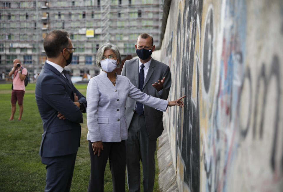 German Foreign Minister Heiko Maas, left, and his counterpart from South Korea Kang Kyung-wha visit the Berlin Wall memorial site in Berlin, Germany, Monday, Aug. 10, 2020. At right Axel Klausmeier, the director of the memorial site. (AP Photo/Markus Schreiber)