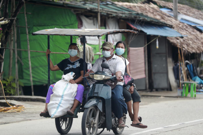 FILE - In this July 28, 2021, file photo, people wearing face masks to help curb the spread of the coronavirus ride a tricycle to transport goods in Shwe Pyi Thar township in Yangon, Myanmar. With coronavirus deaths rising in Myanmar, there are growing allegations from residents and human rights activists that the military government, which seized control in February, is using the pandemic to consolidate power and crush opposition. (AP Photo, File)