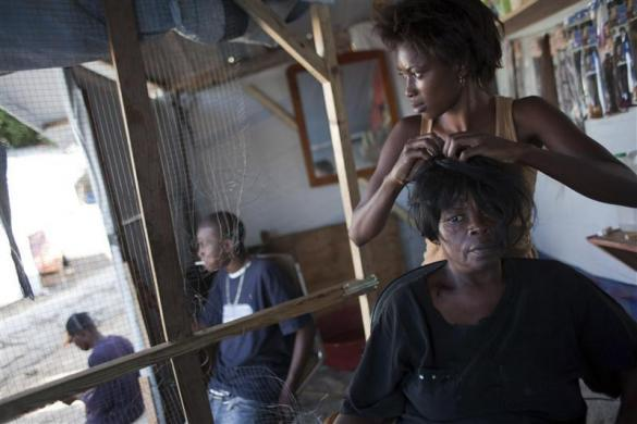 Julie Colin weaves the hair of Marianne Cadet at her beauty salon in the Petionville Club tent camp in Port-au-Prince, November 30, 2010.