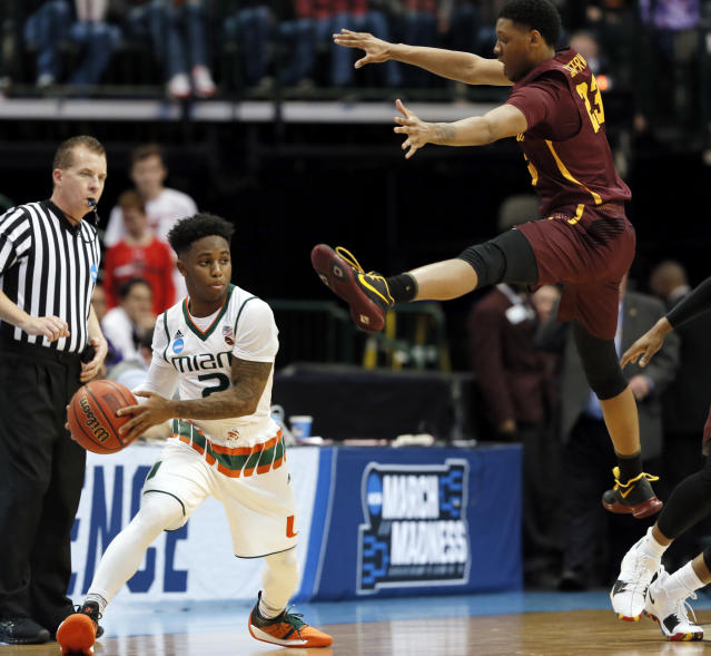 Miami guard Chris Lykes, left, prepares to pass as Loyola-Chicago guard Cameron Satterwhite, right, defends in the first half of a first-round game at the NCAA college basketball tournament in Dallas, Thursday, March 15, 2018. (AP Photo/Tony Gutierrez)