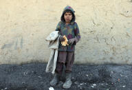 An internally displaced boy poses for a photograph outside his temporary home in the city of Kabul, Afghanistan, Wednesday, Dec. 30, 2020. Save the Children has warned that more than 300,000 Afghan children face freezing winter conditions that could lead to illness, in the worst cases death, without proper winter clothing and heating. (AP Photo/Rahmat Gul)