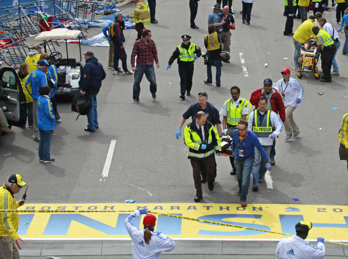 FILE— In this Monday April 15, 2013 file photograph, emergency workers aid injured people at the finish line of the 2013 Boston Marathon following two explosions in Boston. Boston is marking eight years since the bombing at the 2013 Boston Marathon killed three people and injured scores of others. Acting Mayor Kim Janey on Thursday, April 15, 2021, paid a noontime visit to the downtown memorial marking the bombing site. (AP Photo/Charles Krupa, File)