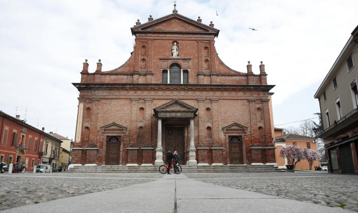 In this photo taken on Thursday, March 12, 2020, a view of the almost empty main square in Codogno, Italy. The northern Italian town that recorded Italy's first coronavirus infection has offered a virtuous example to fellow Italians, now facing an unprecedented nationwide lockdown, that by staying home, trends can reverse. Infections of the new virus have not stopped in Codogno, which still has registered the most of any of the 10 Lombardy towns Italy's original red zone, but they have slowed. For most people, the new coronavirus causes only mild or moderate symptoms. For some it can cause more severe illness. (AP Photo/Antonio Calanni)