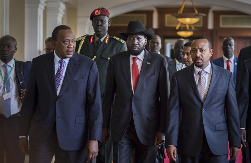 """South Sudan's President Salva Kiir, center, walks with Kenya's President Uhuru Kenyatta, left, and Ethiopia's Prime Minister Abiy Ahmed, right, during peace talks concerning South Sudan's civil war, in Addis Ababa, Ethiopia Thursday, June 21, 2018. South Sudan's armed opposition on Thursday rejected any """"imposition"""" of a peace deal to end the five-year civil war and asked for more time after the first face-to-face meeting between President Salva Kiir and rival Riek Machar in almost two years. (AP Photo/Mulugeta Ayene)"""