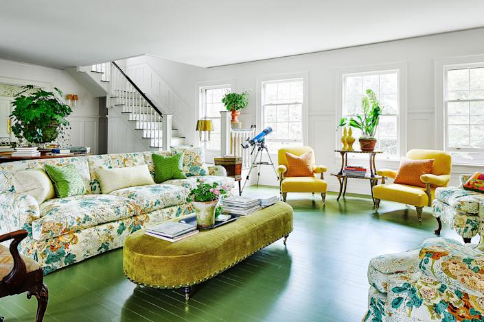 """<div class=""""caption""""> In the living room, a <a href=""""https://www.kravet.com/lee-jofa"""" rel=""""nofollow noopener"""" target=""""_blank"""" data-ylk=""""slk:Lee Jofa"""" class=""""link rapid-noclick-resp"""">Lee Jofa</a> chintz-covered sofa and armchairs, vintage-linen-covered armchairs, and a 19th-century French tiered table surround the ottoman in a <a href=""""http://www.claremontfurnishing.com/"""" rel=""""nofollow noopener"""" target=""""_blank"""" data-ylk=""""slk:Claremont"""" class=""""link rapid-noclick-resp"""">Claremont</a> linen. </div>"""
