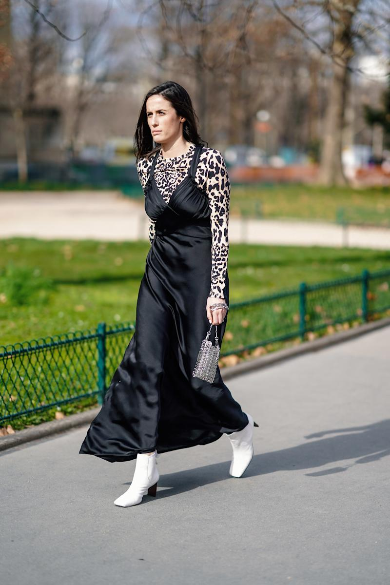 PARIS, FRANCE - FEBRUARY 28: A guest wears a lustrous black satin flowing strappy dress, a leopard print top, white boots, a small metal mesh bag, outside Paco Rabanne, during Paris Fashion Week Womenswear Fall/Winter 2019/2020, on February 28, 2019 in Paris, France. (Photo by Edward Berthelot/Getty Images)