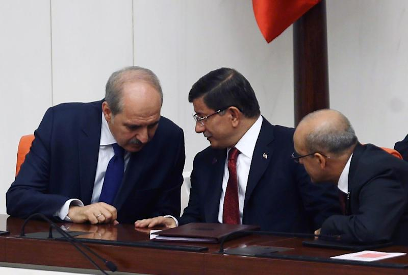Turkish Prime Minister Ahmet Davutoglu (C) huddles with deputy prime ministers Numar Kurtulmus (L) and Mehmet Simsek (R) on November 25, 2015, as tensions soared in the wake of Turkey's downing of a Russian warplane November 24 (AFP Photo/Adam Altan)