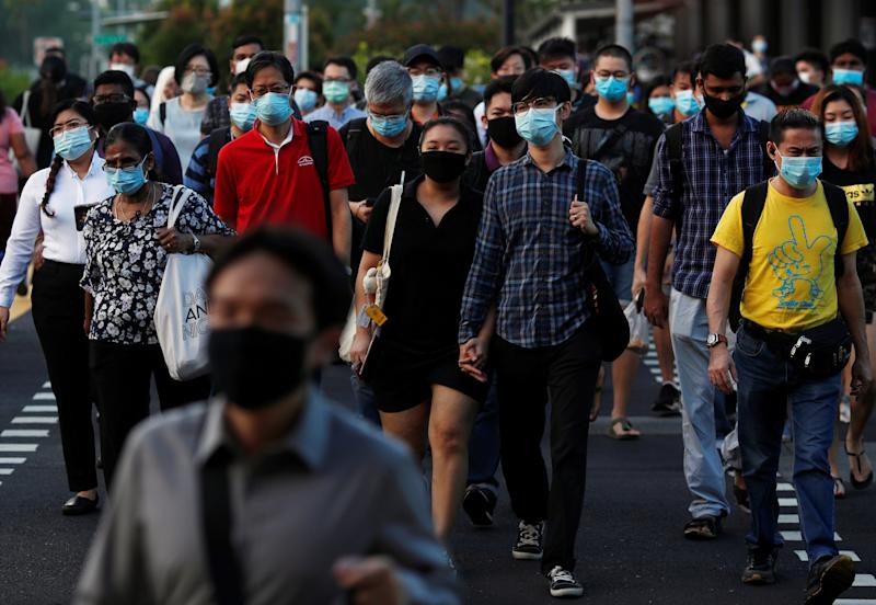 People cross a street during morning peak hour commute amid the coronavirus disease outbreak in Singapore on 3 June, 2020. (PHOTO: Reuters)