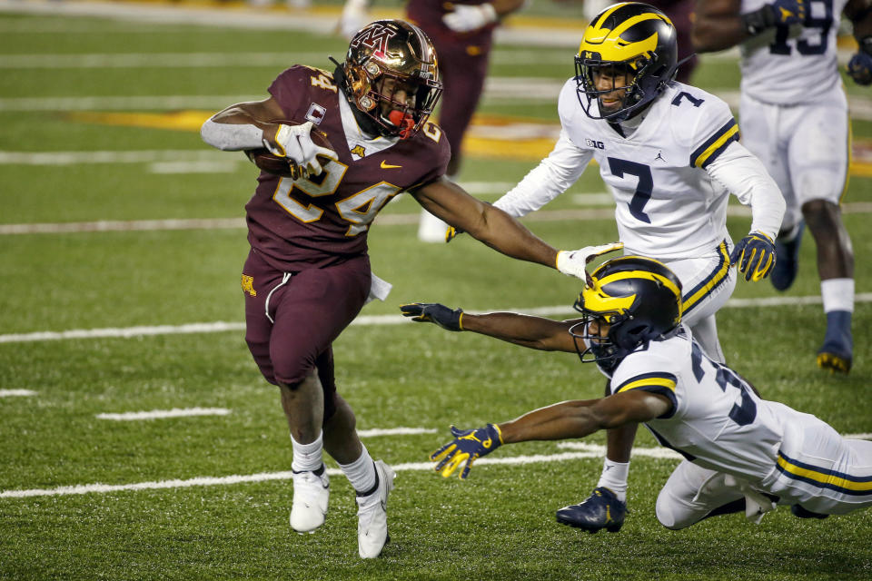 Minnesota running back Mohamed Ibrahim (24) runs for a touchdown past Michigan defensive backs Daxton Hill (30) and Makari Paige (7) in the second quarter of an NCAA college football game Saturday, Oct. 24, 2020, in Minneapolis. (AP Photo/Bruce Kluckhohn)
