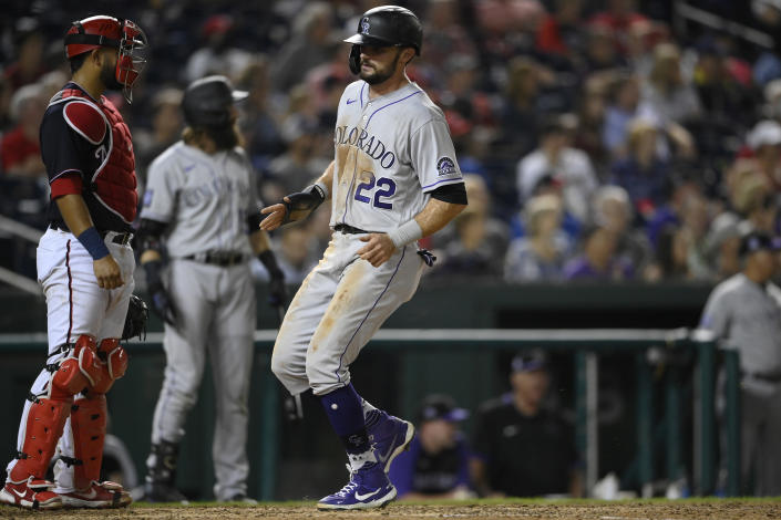 Colorado Rockies' Sam Hilliard (22) comes in to score on a single by Brendan Rodgers during the ninth inning of a baseball game against the Washington Nationals, Friday, Sept. 17, 2021, in Washington. Nationals catcher Keibert Ruiz, left, looks on. (AP Photo/Nick Wass)