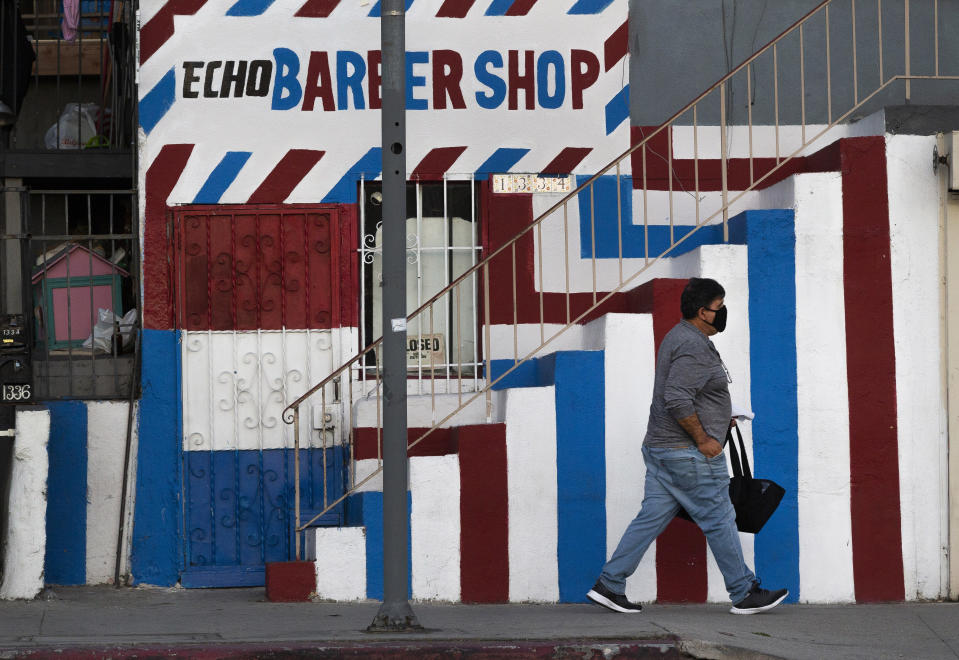 FILE — In this Friday May 8, 2020 file photo A pedestrian wears a mask as he walks past the closed Echo Barber Shop in the Echo Park neighborhood of Los Angeles. California Health and Human Services Secretary Dr. Mark Ghaly explained the math behind the state's calculation of when it is safe to lift it's stay-at-home order and overnight curfew, during a news briefing Tuesday, Jan. 26, 2021. (AP Photo/Damian Dovarganes, File)