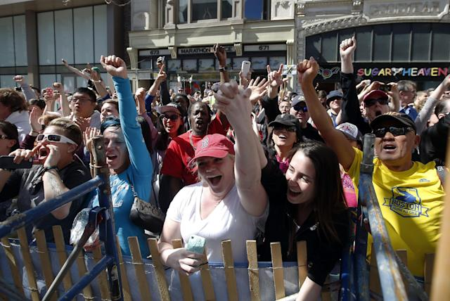 Race fans cheer runners in front of the Marathon Sports store, site of the the first bomb blast last year, near the finish line of the 118th Boston Marathon Monday, April 21, 2014 in Boston. (AP Photo/Elise Amendola)