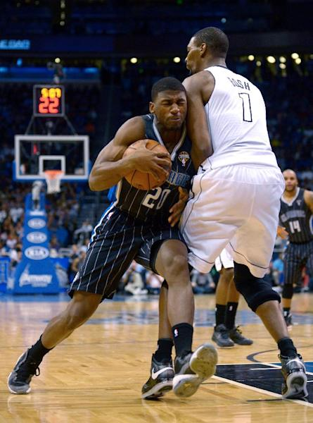 Orlando Magic forward DeQuan Jones (20) collides with Miami Heat forward Chris Bosh (1) while driving to the basket during the first half of an NBA basketball game in Orlando, Fla., Monday, March 25, 2013. (AP Photo/Phelan M. Ebenhack)