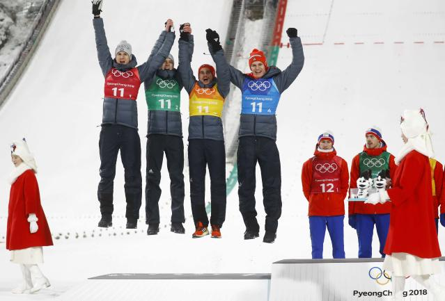 Ski Jumping - Pyeongchang 2018 Winter Olympics - Men's Team Final - Alpensia Ski Jumping Centre - Pyeongchang, South Korea - February 19, 2018 - Silver medalists Karl Geiger, Stephan Leyhe, Richard Freitag and Andreas Wellinger of Germany celebrate on the podium during the victory ceremony. REUTERS/Kai Pfaffenbach