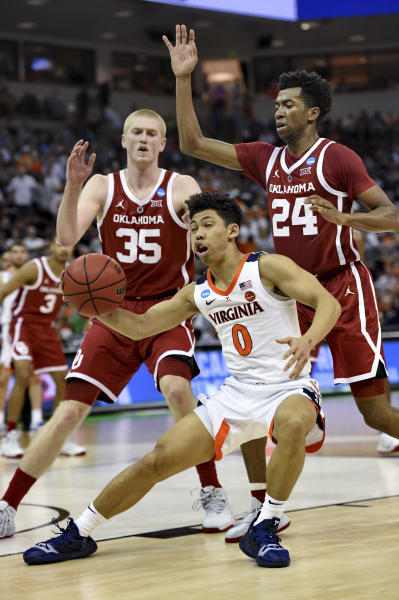 Virginia's Kihei Clark (0) is pressured under the basket by Oklahoma's Brady Manek (35) and Jamal Bieniemy (24) during the second half of a second-round men's college basketball game in the NCAA Tournament in Columbia, S.C., Sunday, March 24, 2019. (AP Photo/Richard Shiro)