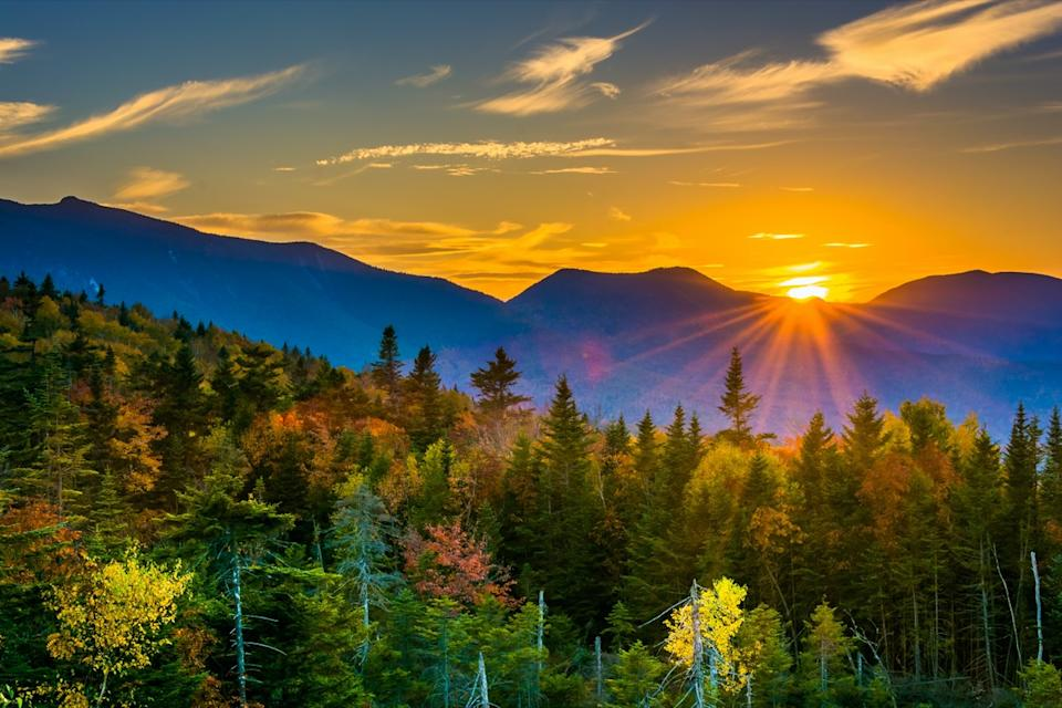 sunset over the peaks of a mountain in autumn