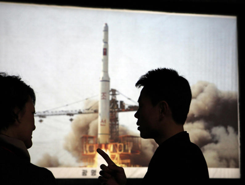 "FILE - In this Tuesday, April 10, 2012 file photo, North Korean guide Kim Won Ho, right, speaks to a foreign journalist near a photo depicting the 2009 satellite rocket launch at the Three Revolutions exhibition hall in Pyongyang, North Korea. According to North Korea's official version of things, commemorated on postage stamps and re-enacted in mass performances, the country's first venture into space was 14 years ago, when the ""Bright Shining Star 1"" satellite roared into orbit and began broadcasting marching music praising Kim Il Sung. (AP Photo/Ng Han Guan, File)"
