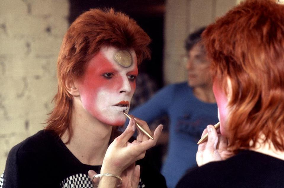 David Bowie applies makeup during his Ziggy Stardust incarnation.